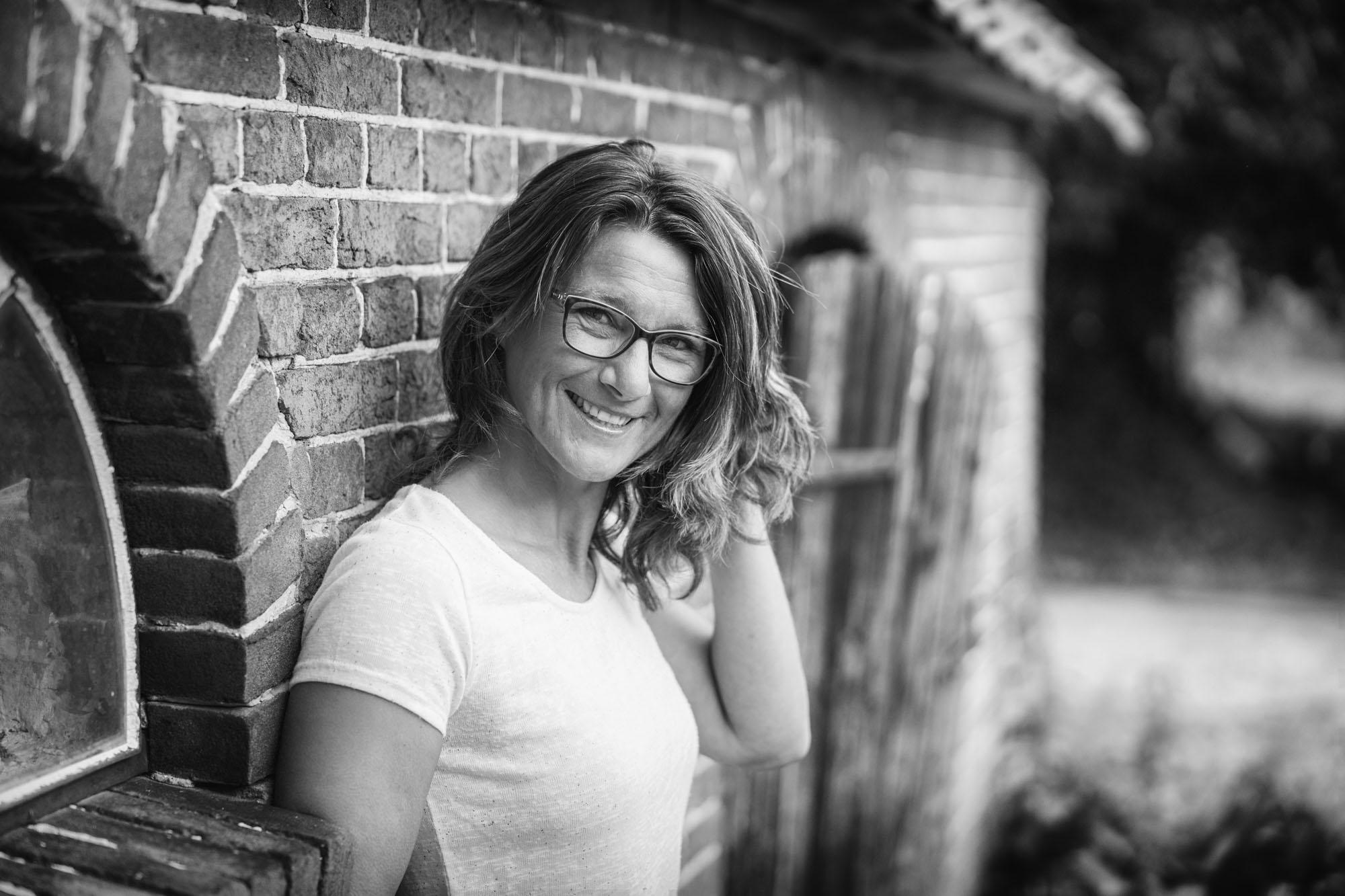 Zwart-wit portret van lachende vrouw bij oude stenen muur door MayraFotografie