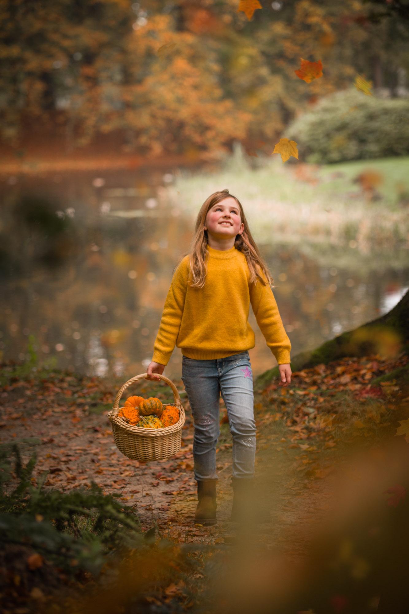 Meisje met mandje pompoenen in herfst bos