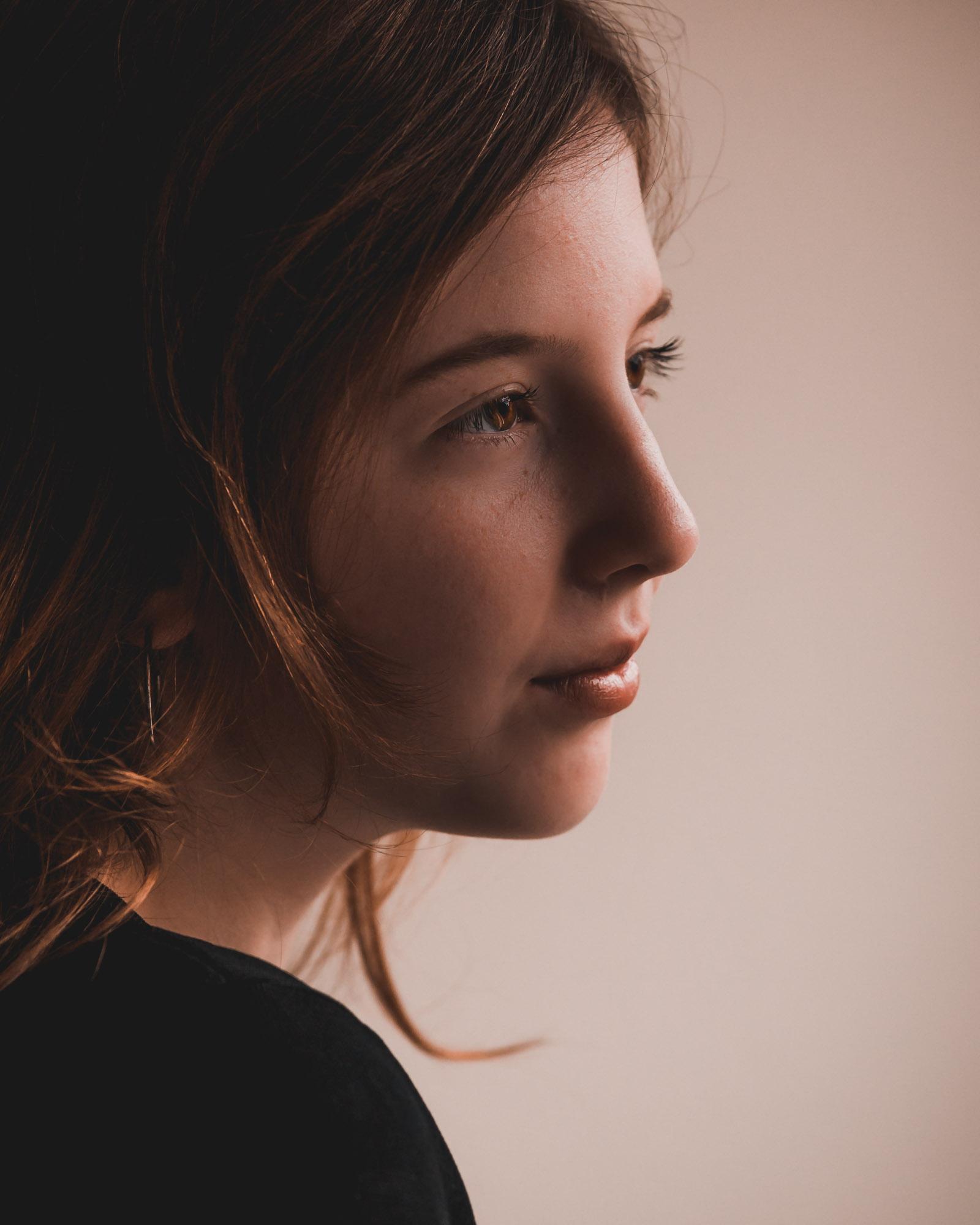 moody portret van jonge vrouw in natuurlijk licht door mayrafotografie
