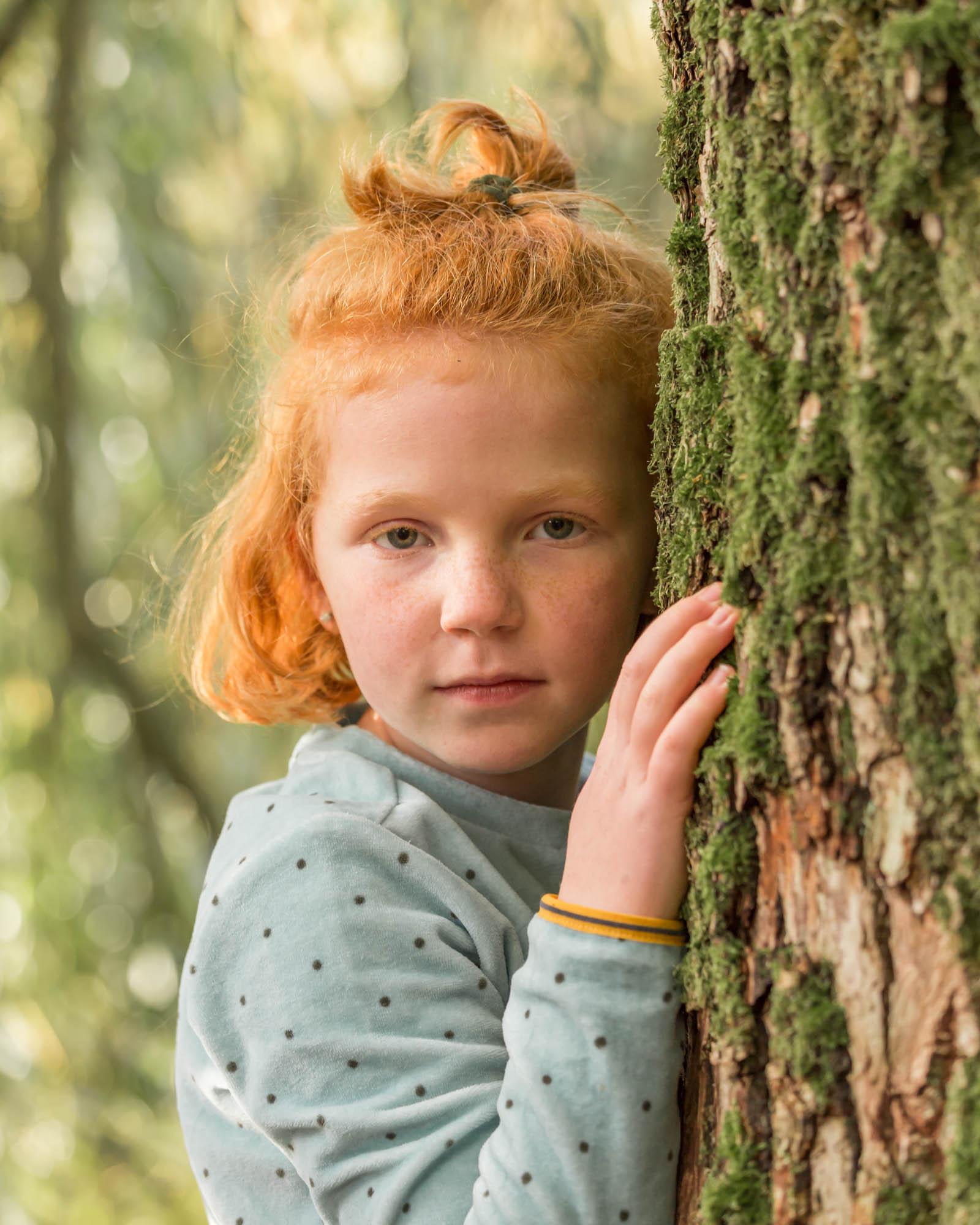 natuurlijk portret van meisje met rood tegen groen boomschors door mayrafotografie