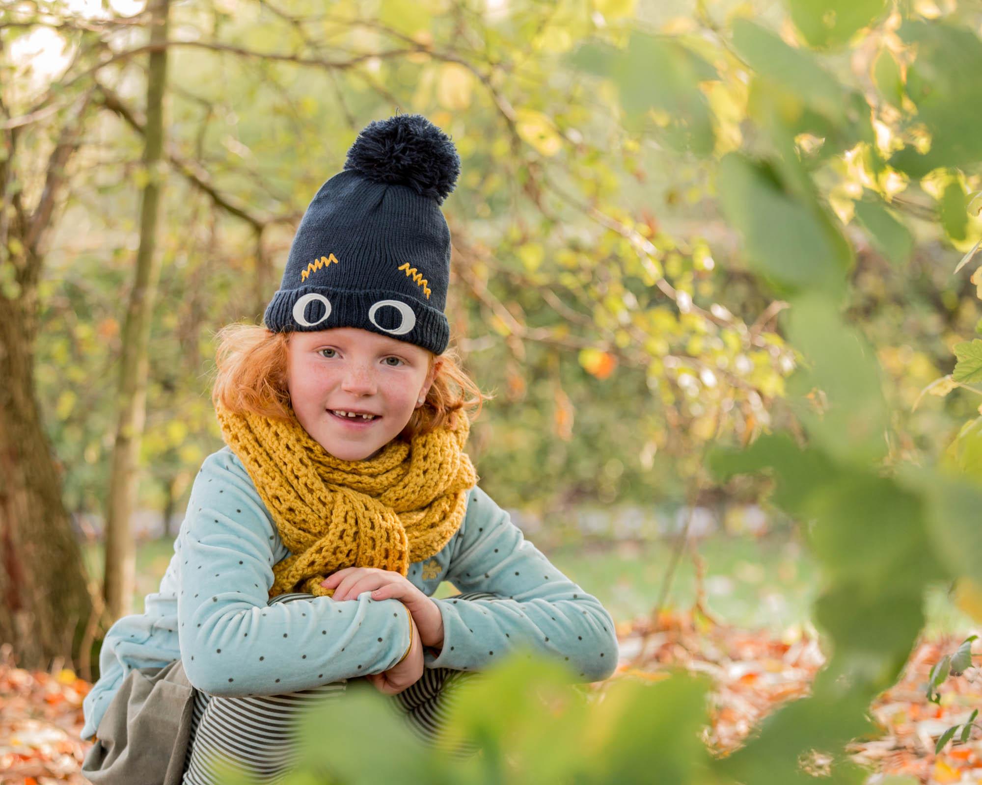natuurlijk buiten portret van meisje met muts tussen groene bladeren door mayrafotografie