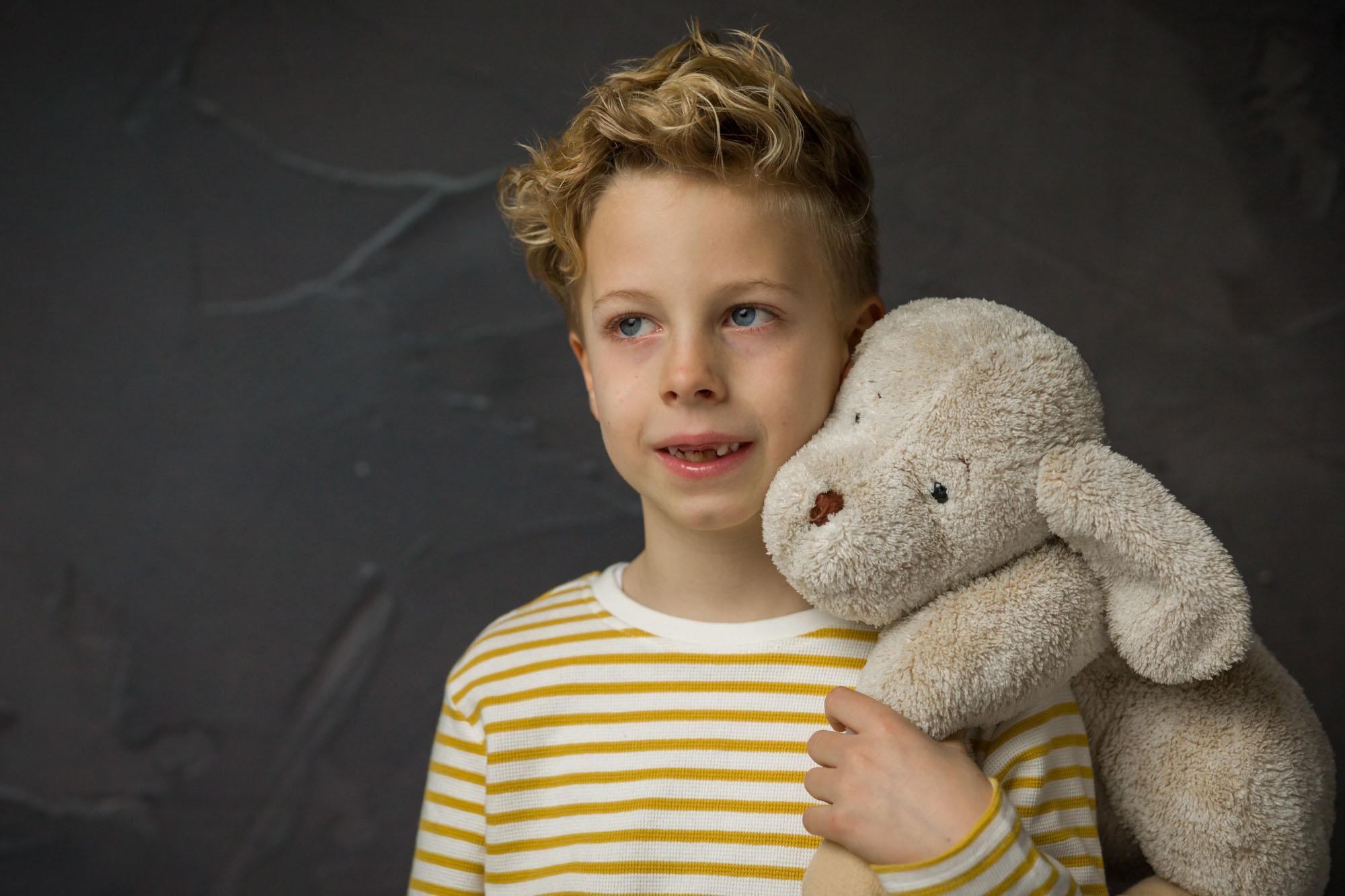 portret van blonde jongen met knuffel in studio met natuurlijk licht door MayraFotografie