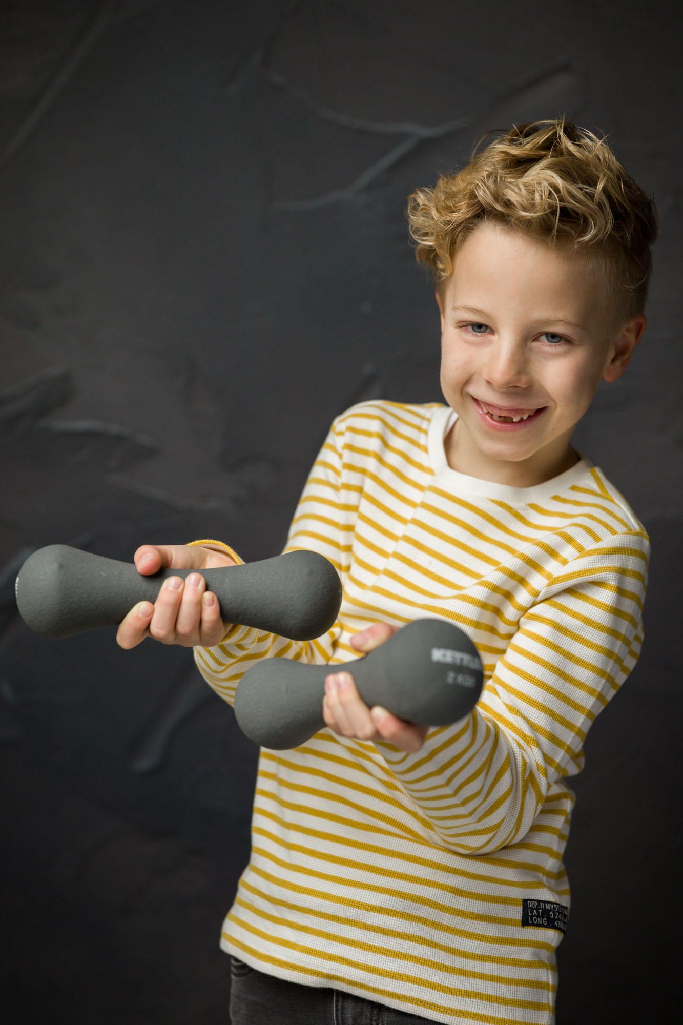 portret van lachende jongen met gewichtjes in studio met natuurlijk licht door MayraFotografie