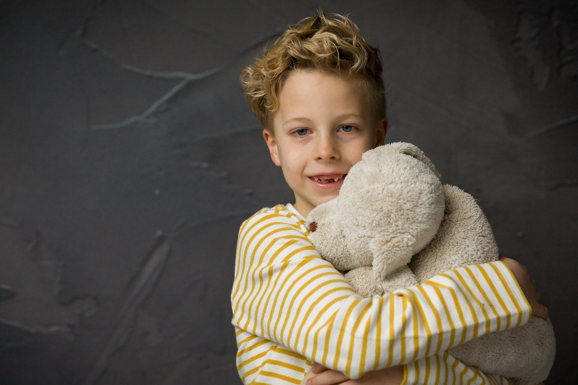 portret van lachende jongen met knuffel in studio met natuurlijk licht door MayraFotografie