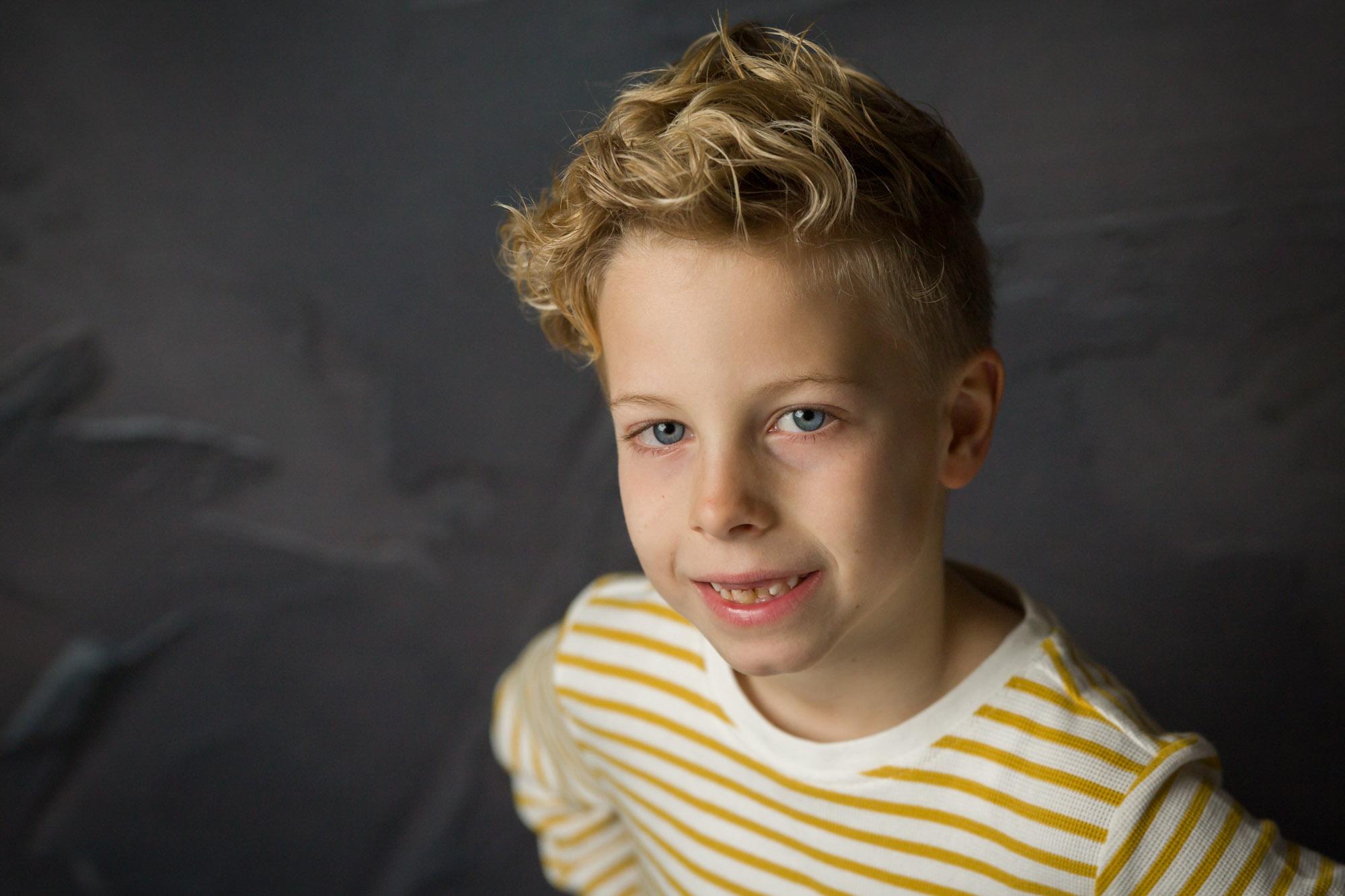 portret van blonde lachende jongen in studio met natuurlijk licht door MayraFotografie