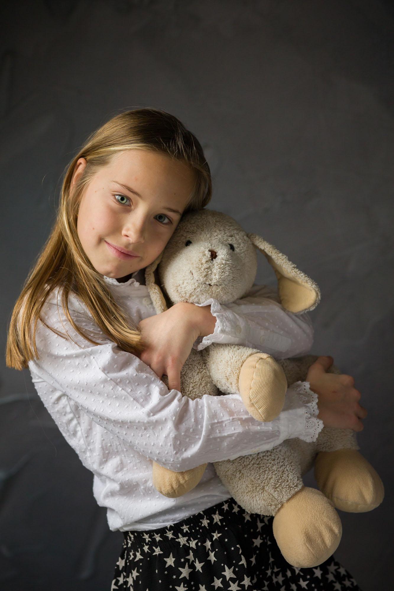 portret van jong meisje met knuffel in studio met natuurlijk licht door MayraFotografie