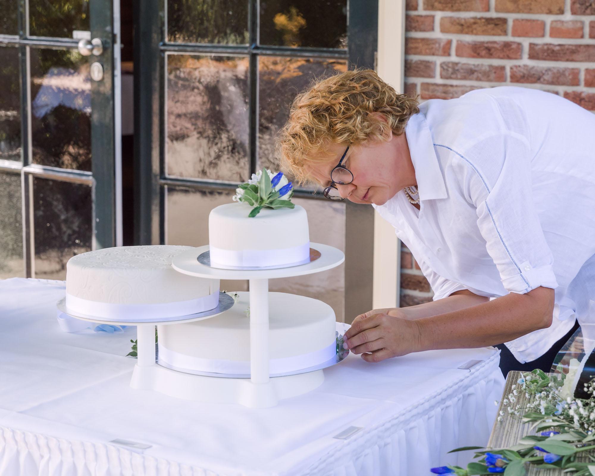 foto van vrouwelijke zzper bruidstaart aan het decoreren voor personal branding door mayrafotografie