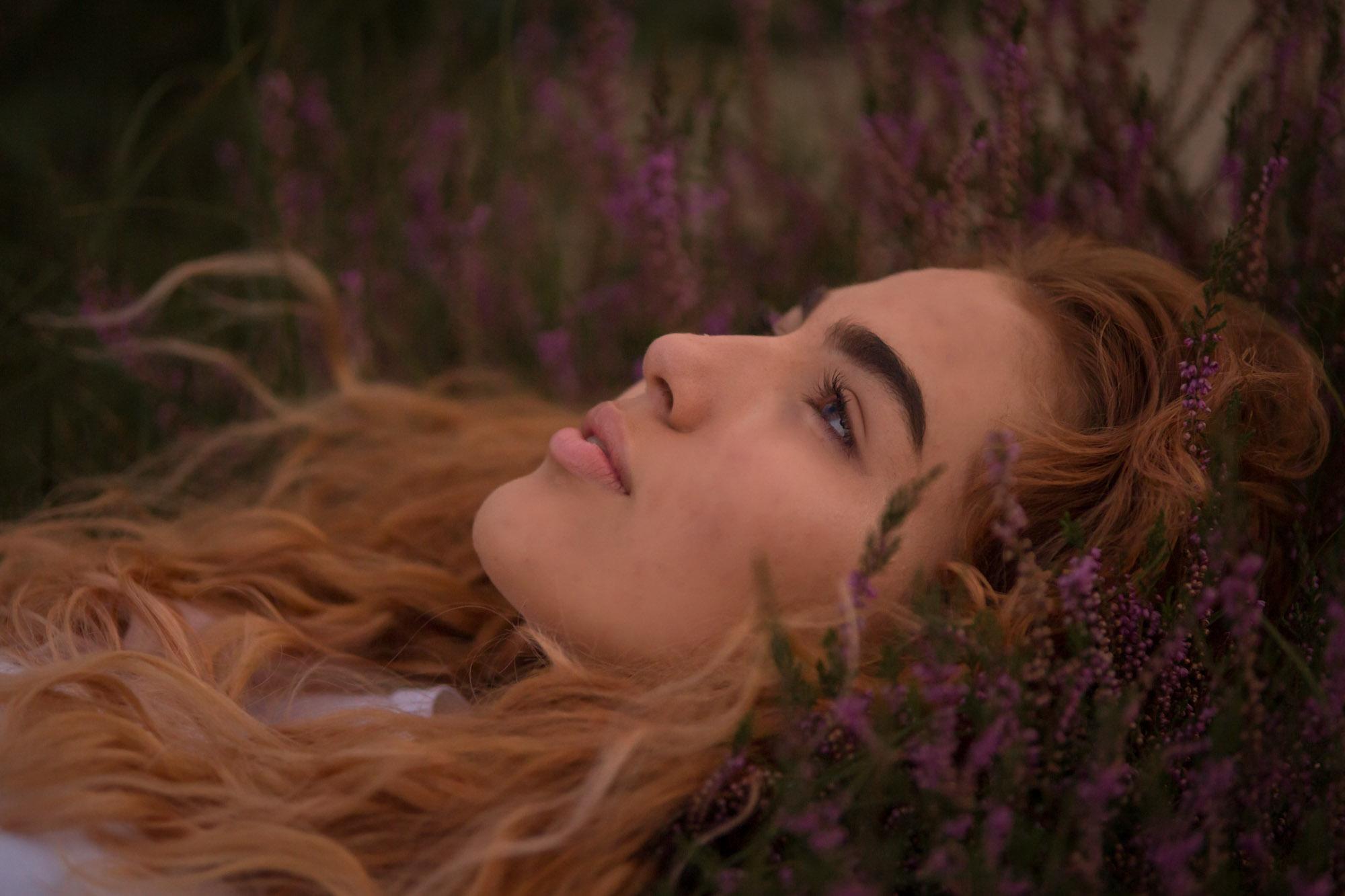 portret van jonge vrouw liggend in bloeiende heide door mayrafotografie