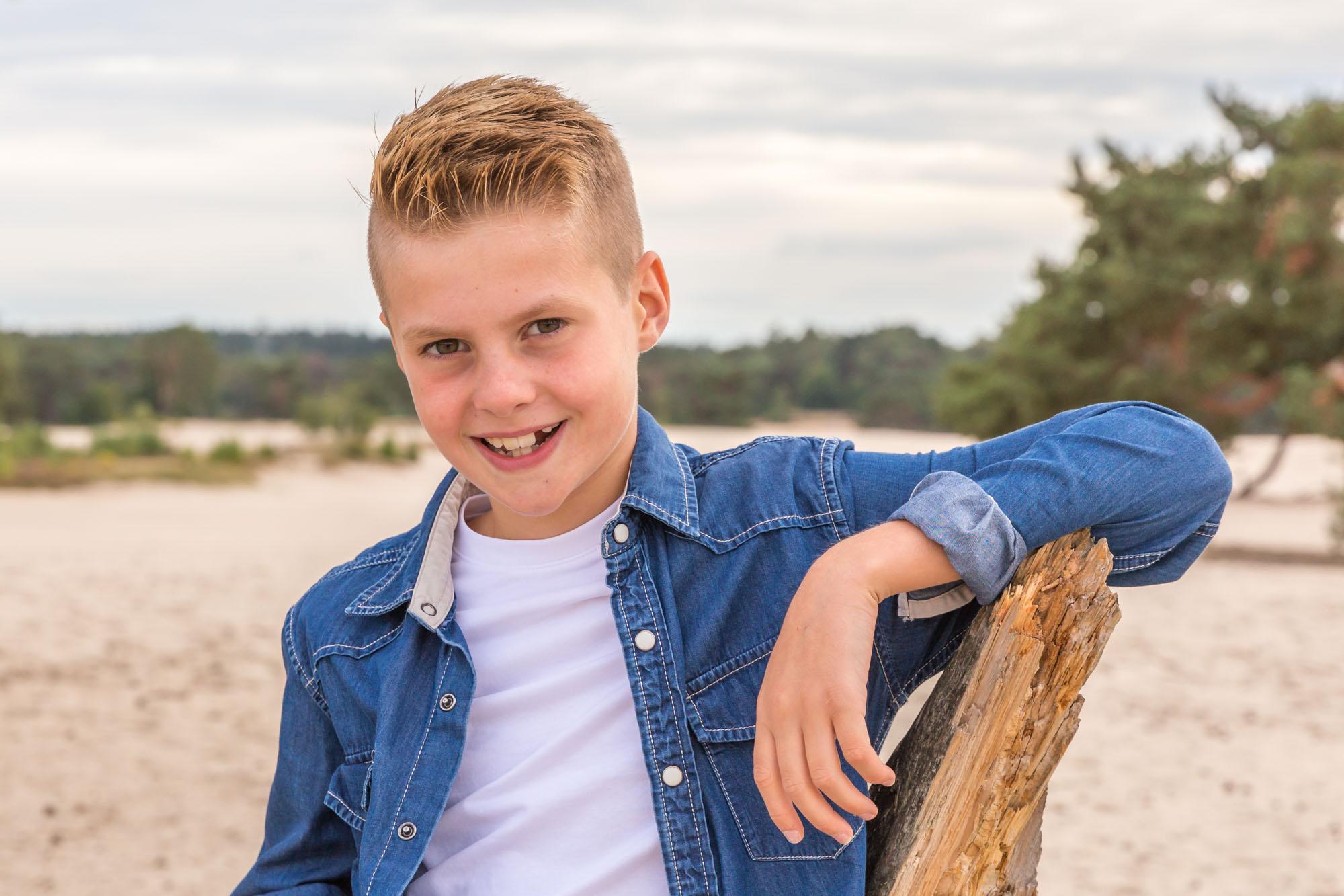 kind portret van blonde jongen bij boomstronk door mayrafotografie