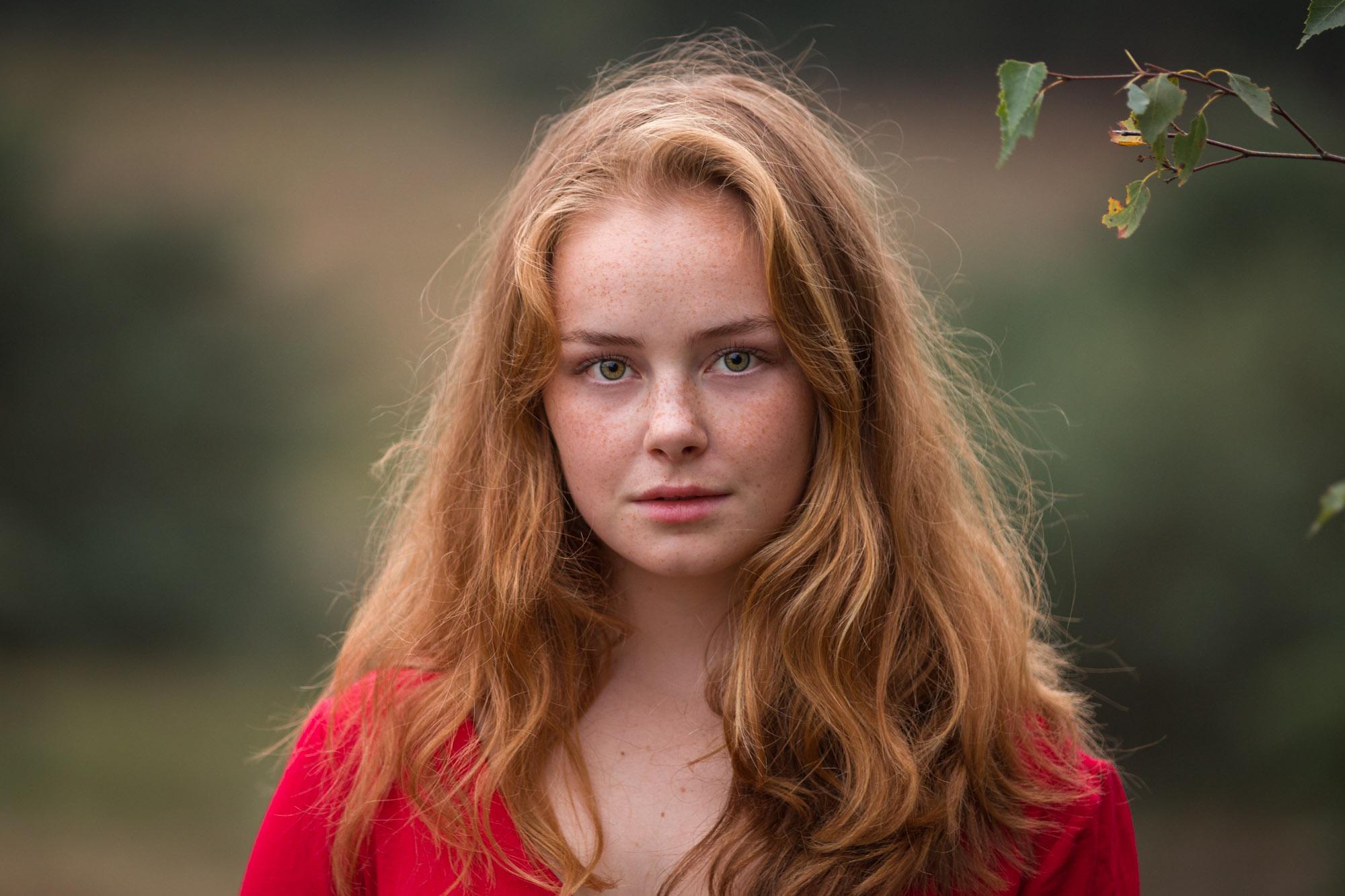 buiten portret van jonge vrouw met rood lang haar en sproeten en rode jurk door mayrafotografie