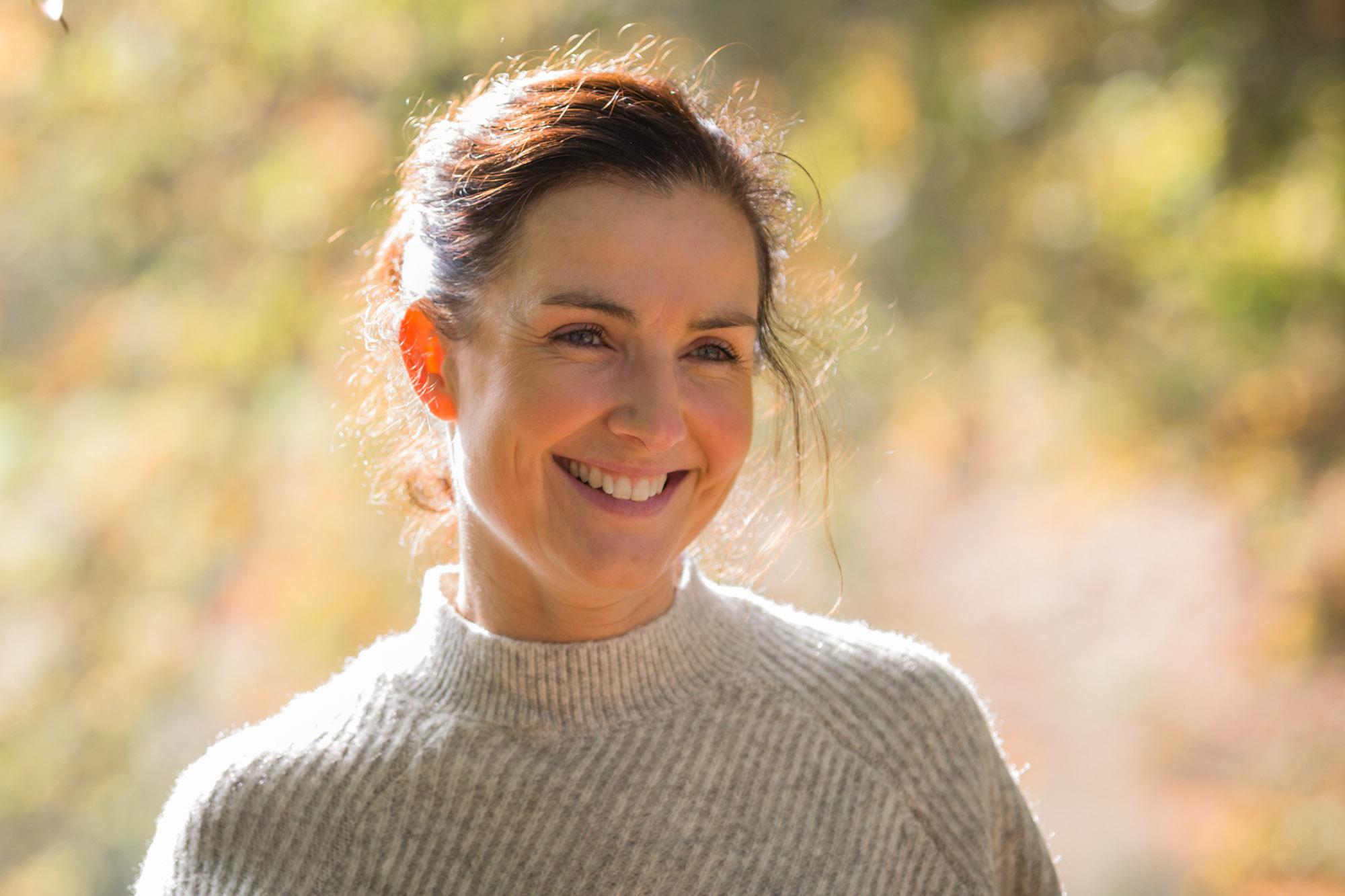 Portret van lachende vrouw met wollen trui in de herfst