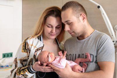 foto van ouders met prematuur baby met roze kleertjes voor stichting earlybirds door mayrafotografie