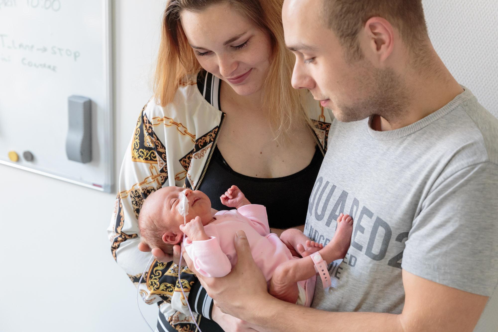 foto van vader en moeder met prematuur baby met roze kleertjes voor stichting earlybirds door mayrafotografie