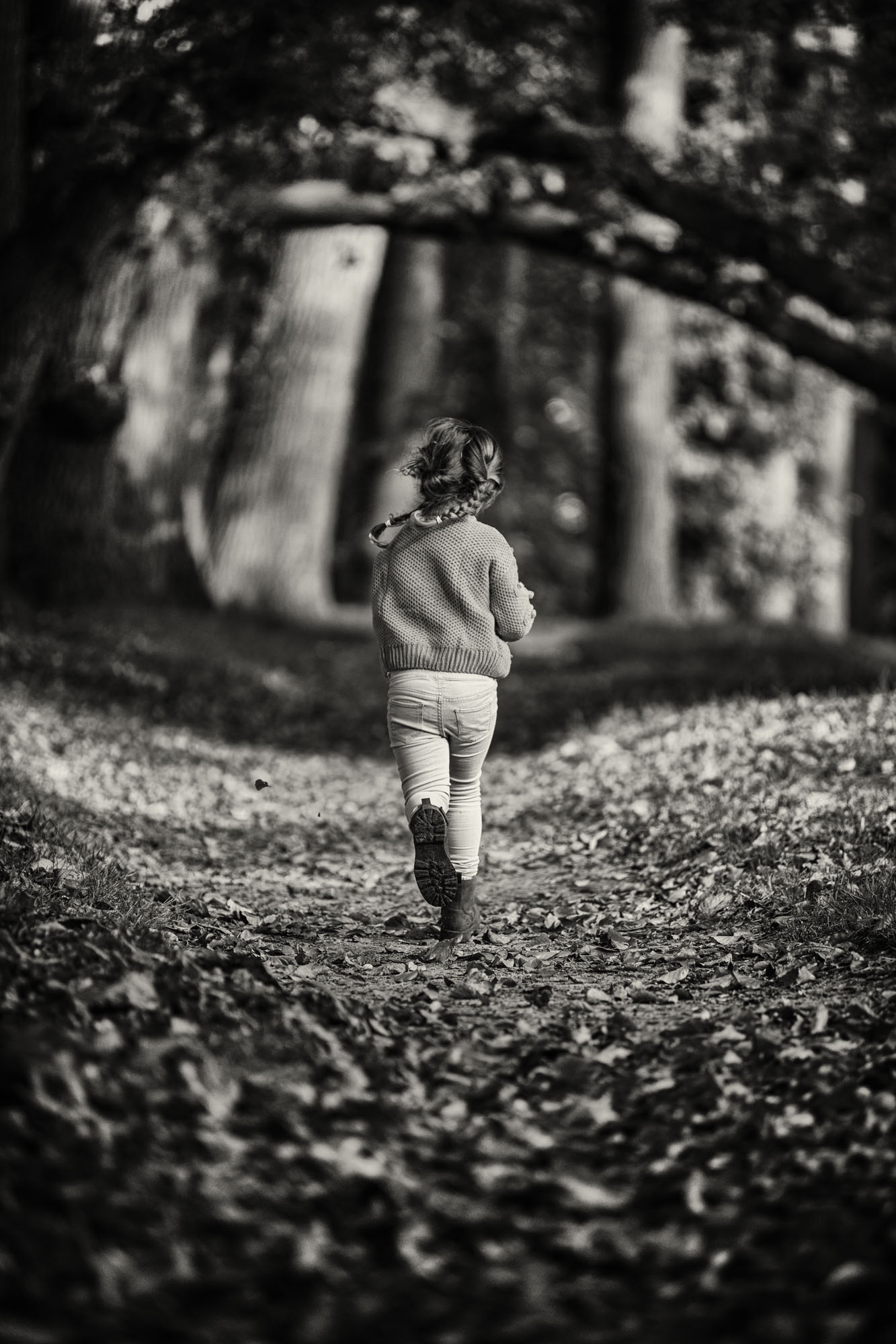 Zwartwit foto van rennend meisje met vlechtjes op bospad