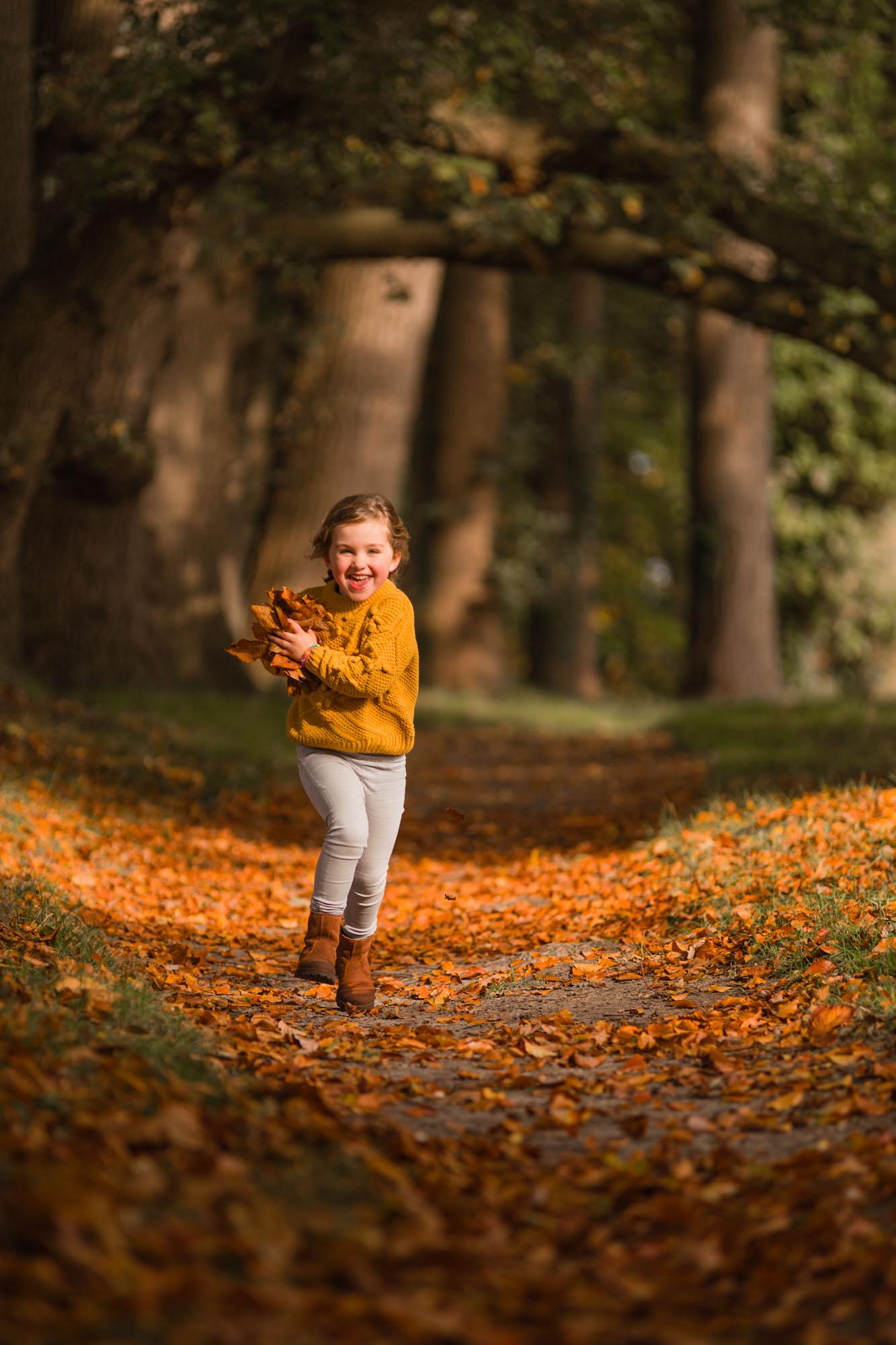 Rennend meisje met handvol herfstbladeren in bos