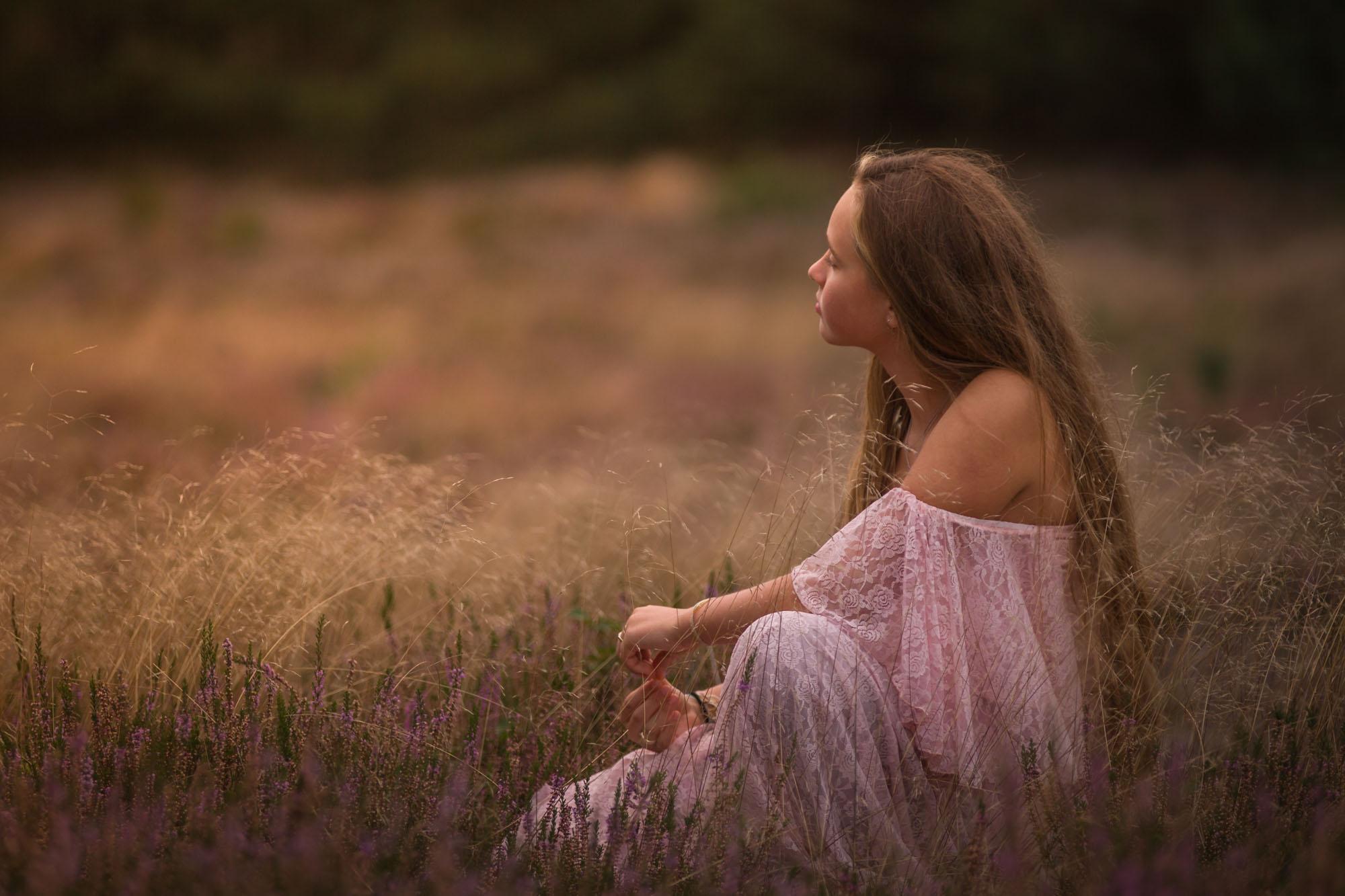 romantisch portret van jonge vrouw zittend in gras en heide door mayrafotografie