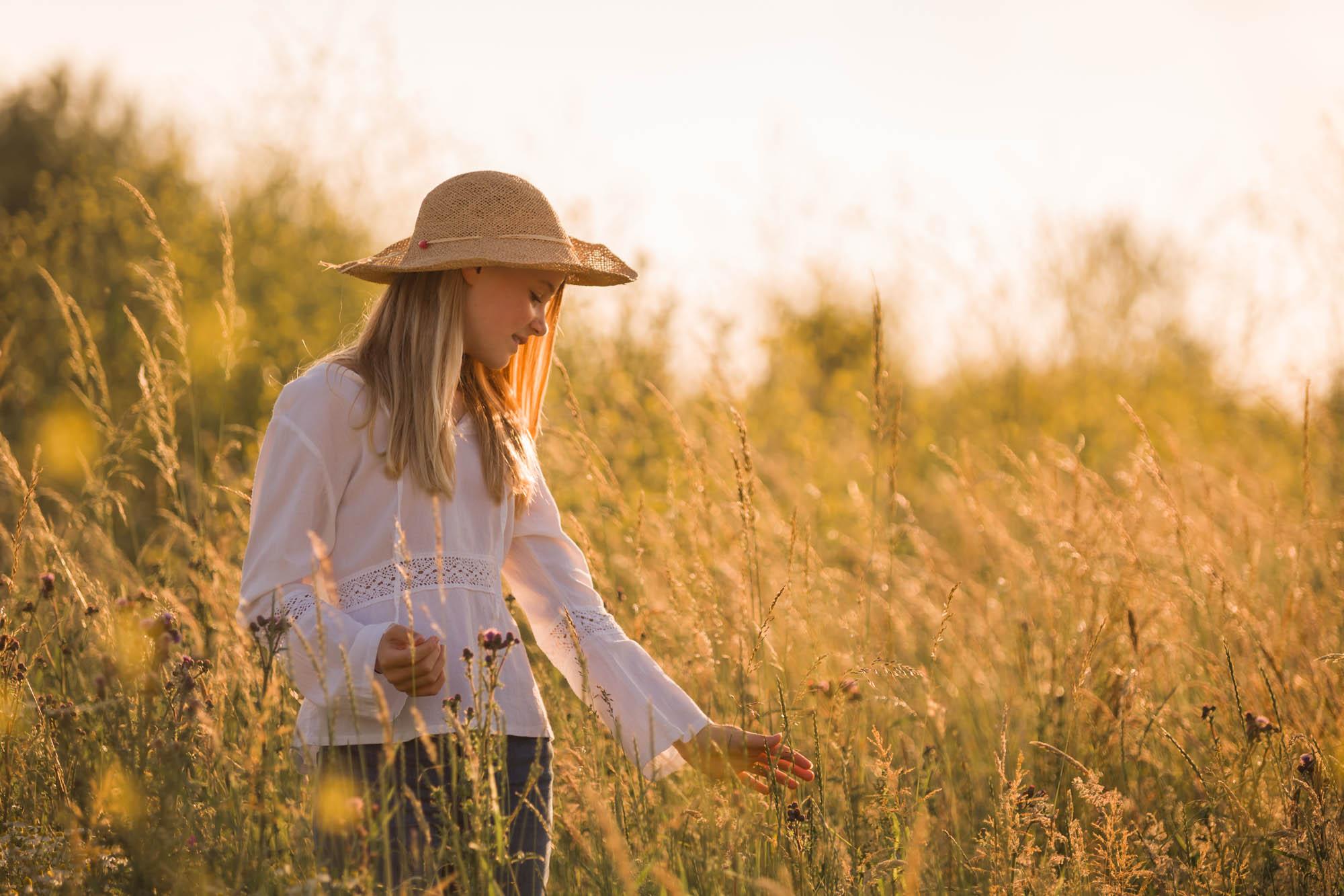Romantisch portret van meisje met strohoedje tussen hoog gras tijdens het gouden uurtje door MayraFotografie