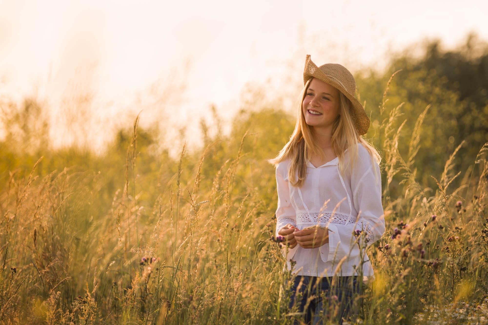 Romantisch portret van blond meisje tussen hoog gras tijdens het gouden uurtje door MayraFotografie