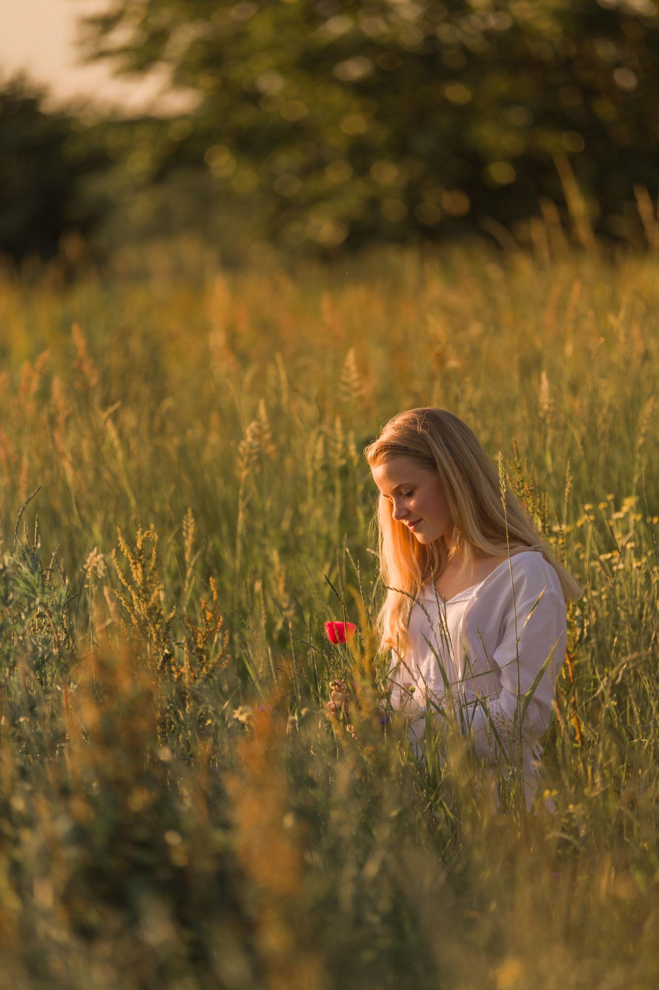 Dromerig portret van blond meisje met klaproos tussen hoog gras door MayraFotografie