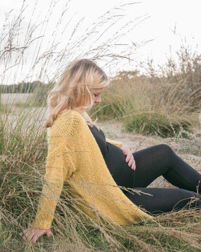 foto van zwangere vrouw met geel vest bij hoog gras door mayrafotografie
